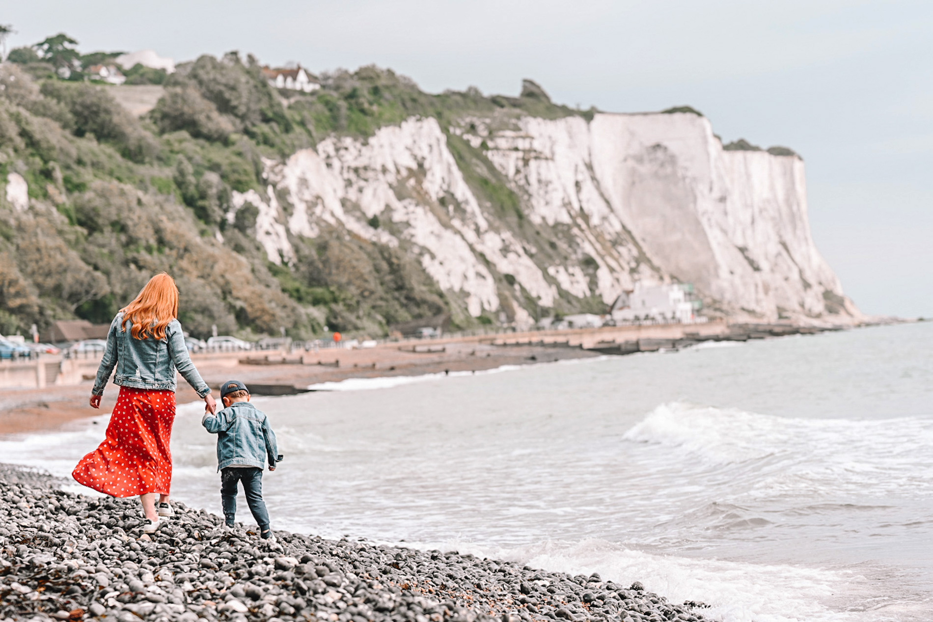 Amber and Max walking along a pebble beach at the white cliffs of Dover